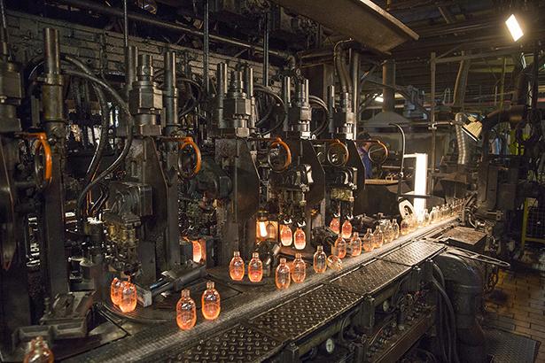 Egy dolgozó az üveggyártó gép formakenését végzi az öblösüveggyárban Fotó: Rosta Tibor/MTI